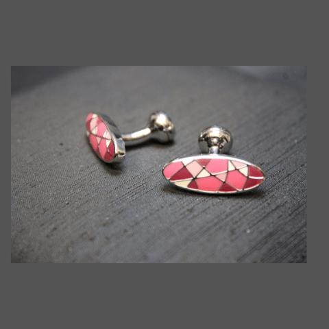 Gemelos de forma ovalada con piedras en tonos rosas.