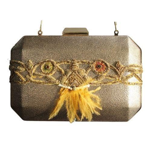 bolso dorado con adorno plumas