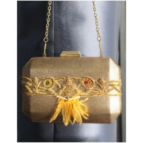 bolso fiesta dorado con adorno plumas naranja